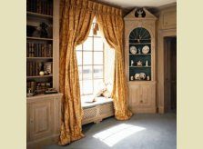 A Hallidays corner cabinet with richly carved pediment, alongside a window seat with concealed radiator and Georgian style bookcase