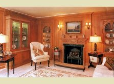 A stained and waxed Hallidays panelled drawing room with display alcoves, hand carved mantlepiece and glazed cabinet.