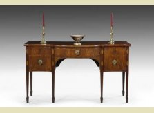 Geroge III mahogany serpentine front sideboard, with Paris porcelain tazza and brass Princess candlesticks