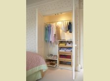 Built in illuminated, painted wardrobe with slide out shelving and shoe trays