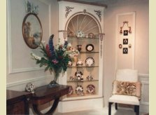 Painted corner display cabinet with delicate hand carved mouldings