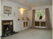 Painted panelled room with matching brass grilles to radiator covers and cupboard doors