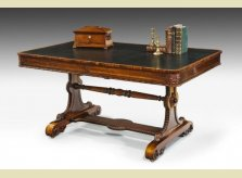A rosewood veneered Regency period Library Table with leathered surface and detailed carving