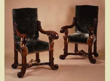 A pair of Italian throne chairs with heavily carved walnut frames