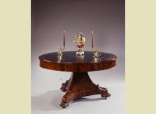 A Regency period library drum table with leather top, on triform base, with brass Griffen candlesticks and porcelain figure