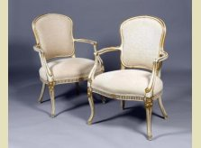 A pair of George III upholstered and painted armchairs